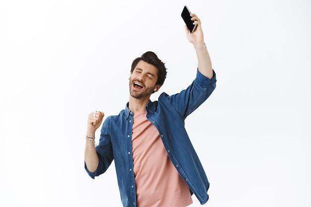 Guy werd meegesleept door muziek, armen omhoog, dansen met gesloten ogen, liedjes luisteren in draadloze koptelefoon, smartphone vasthouden, vuist pompen met ontspannen zorgeloze uitdrukking, meezingen, witte muur