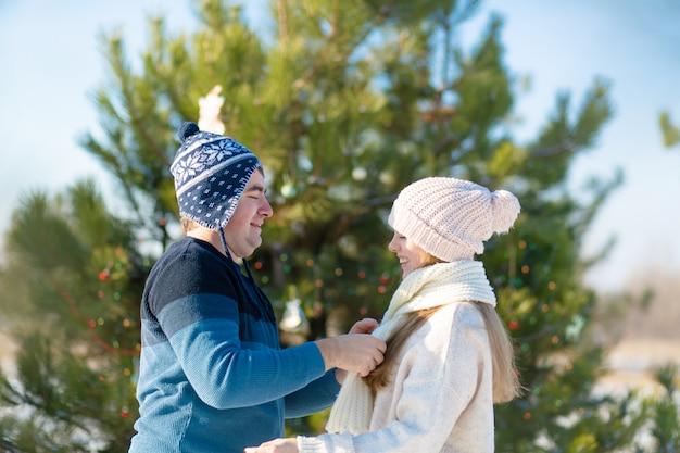 Guy wikkelt een meisje in een warme witte sjaal terwijl hij door een besneeuwd winterbos loopt
