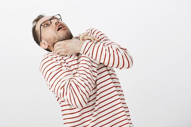 Guy wil zelfmoord plegen om niet meer naar saaie verhalen te luisteren. portret van grappige europese man in glazen, hand in hand op nek en achteruit buigen