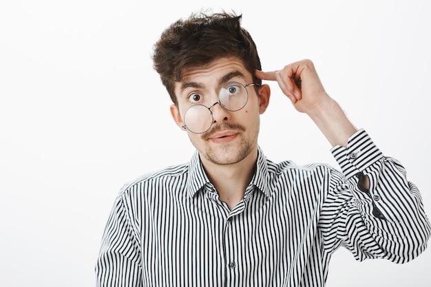 Guy wordt gek na een nacht op het werk. portret van moe en gestrest rommelig mannelijk model met baard en snor, rollende wijsvinger op tempel, verward en beu, staande over grijze muur