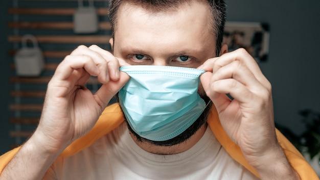 Guy zet een ademhalingsmasker op. aantrekkelijke man zet gezichtsmasker en kijkt naar de camera