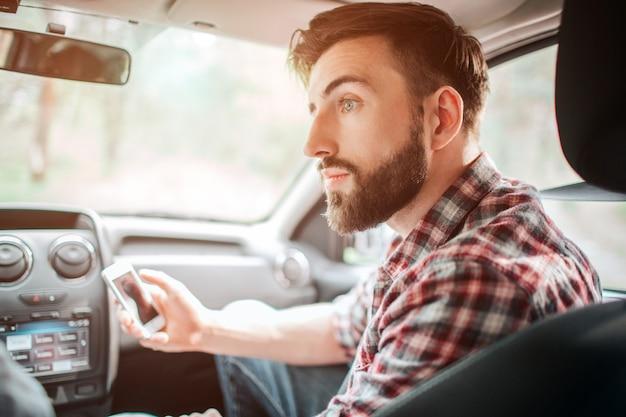 Guy zit in de auto en houdt witte telefoon in zijn handen. hij kijkt verwonderd naar links. man houdt de telefoon bij hem vandaan.