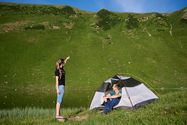Guy zit in de tent en het meisje wijst naar de top van de berg. mooi groen landschap van een bergmeer tegen een achtergrond van een groene berg op een zonnige dag