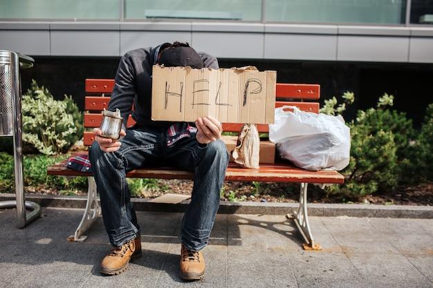 Guy zit op een bankje en houdt een karton met hulpwoord erop