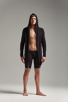 Guy zwemmer in een pet, masker en badjas om te zwemmen, op een grijze achtergrond, voorbereiden op het zwemmen.
