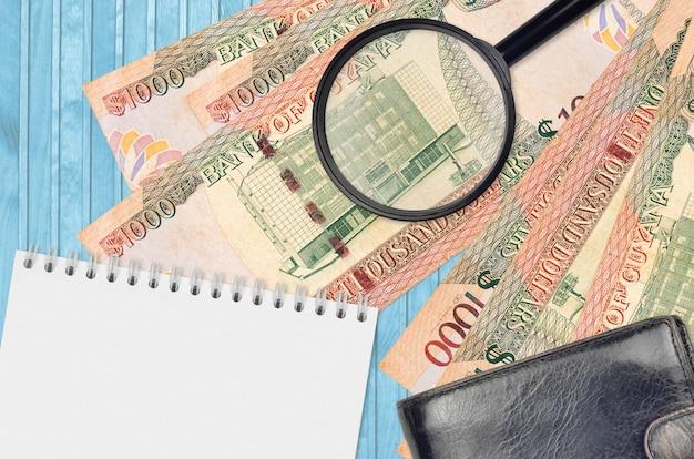 Guyanese dollarsrekeningen en vergrootglas met zwarte beurs en blocnote
