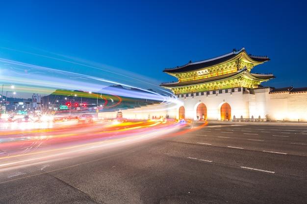 Gyeongbokgung palace, auto's passeren voor gwanghuamun poort na zonsondergang in het centrum van seoul, zuid-korea. naam van het paleis 'gyeongbokgung'