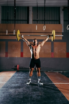 Gym concept met man training met barbell