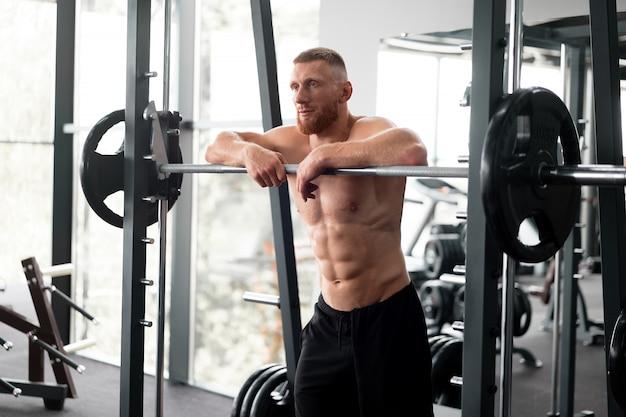 Gym man leunend barbell rust na harde training.
