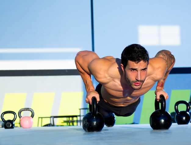 Gym man push-up sterkte push-up met kettlebell