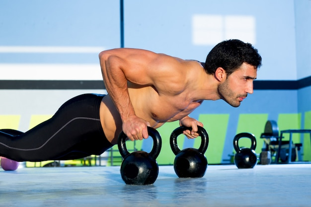 Gym man push-up sterkte push-up met kettlebell