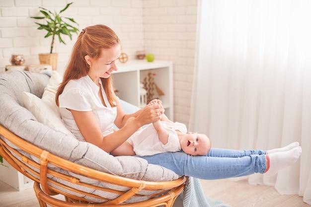 Gymnastiek baby. vrouw die oefeningen met baby voor zijn ontwikkeling doet. masseer een kleine pasgeboren baby.