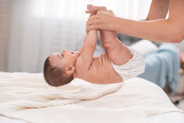 Gymnastiek voor de baby. een moeder tilt haar kind op bij de armen en benen.