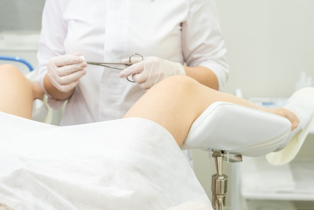 Gynaecologie arts die vrouwelijke patiënt op gynaecologische tang van de stoelholding onderzoekt