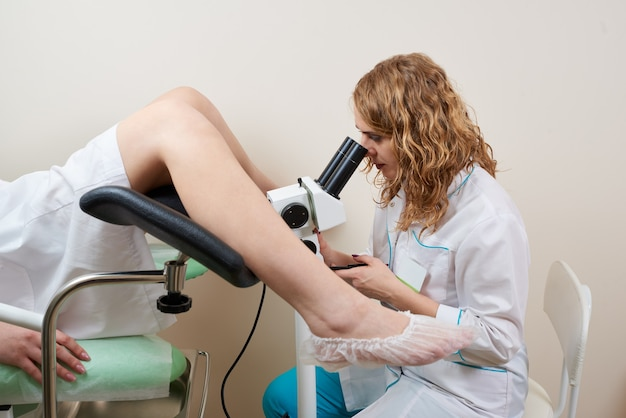 Gynaecoloog behandeling van een patiënt met een microscoop in moderne medische kliniek