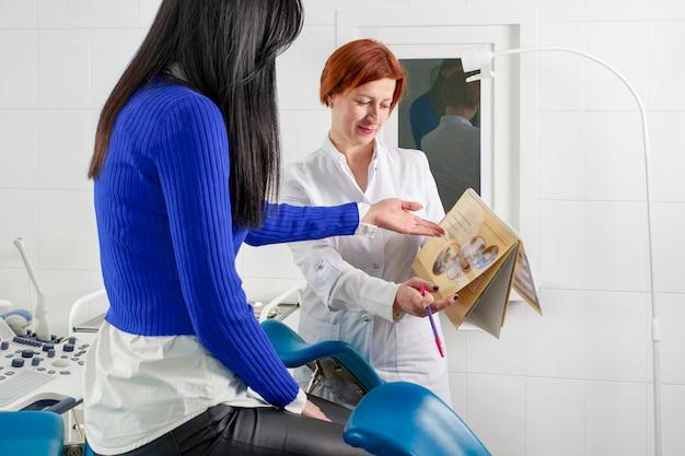 Gynaecoloog die een foto met baarmoeder toont aan een jonge vrouwelijke patiënt, die de kenmerken van de gezondheid van vrouwen uitlegt tijdens een medisch consult op kantoor