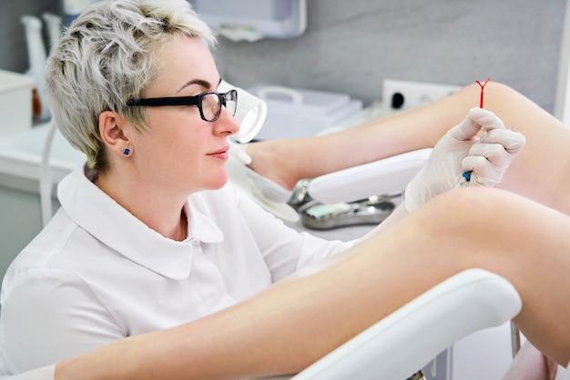 Gynaecoloog die een iud-anticonceptiemiddel vasthoudt voordat het voor de patiënt wordt gebruikt