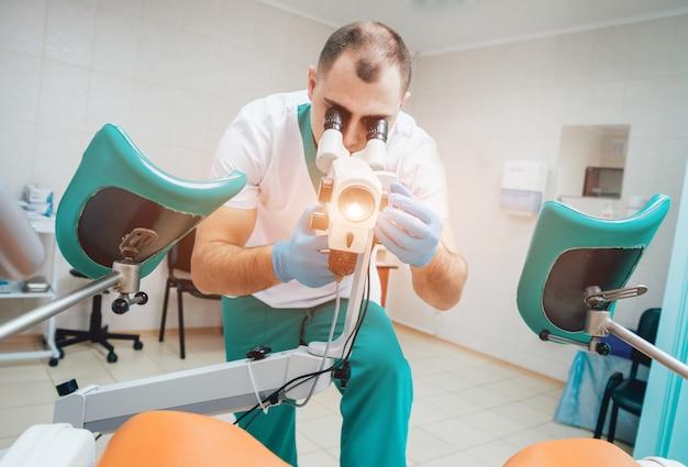 Gynaecoloog die met colposcoop in kliniek werkt.