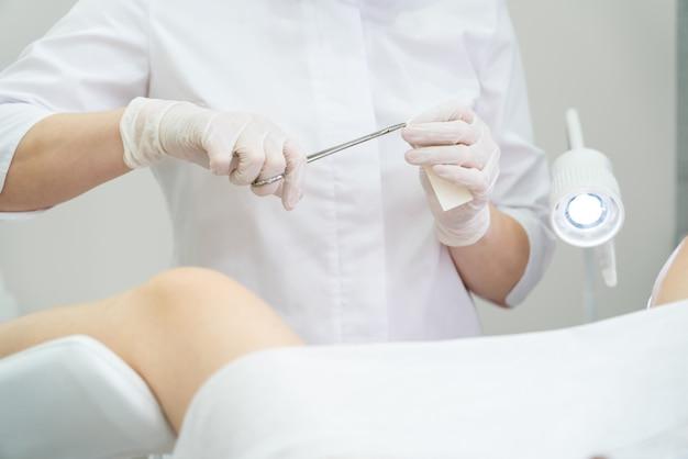 Gynaecoloog die pleister met tang opent