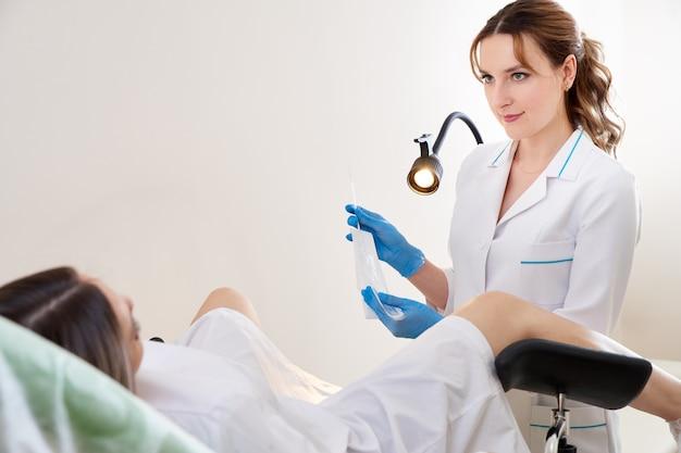Gynaecoloog die vaginale uitstrijkjes gebruikt voor soa-testen. vrouw in gynaecologische stoel
