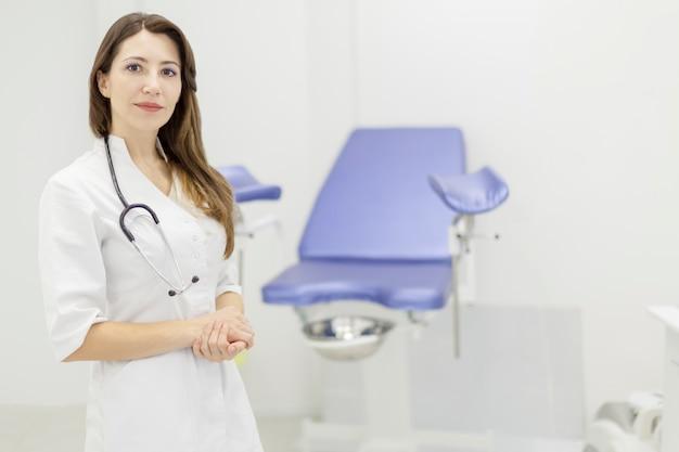 Gynaecoloog in wit uniform in ziekenhuiskliniek met stoel