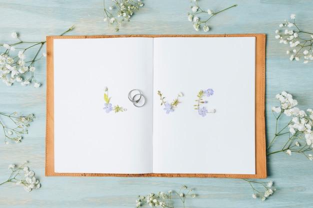 Gypsophilabloem rond de liefdetekst op wit paginaboek over het houten bureau