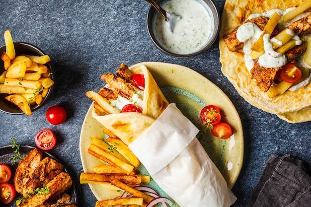 Gyros souvlaki wraps in pitabroodje met kip, aardappelen en tzatziki saus, ingrediënten achtergrond.