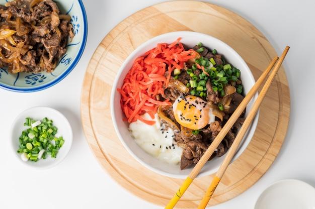 Gyudon japans rundvlees en rijst, traditioneel japans gerecht gyudon gemaakt van dun gesneden rundvlees, ui, sojasaus en rijst, voedselconcept achtergrond