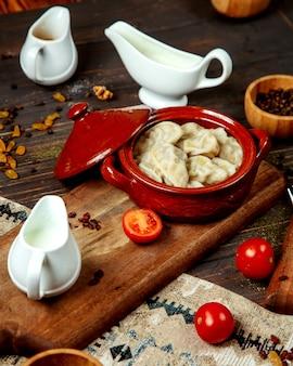 Gyurza met gevuld vlees en katyk op een houten voet
