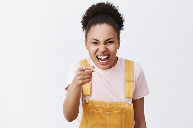 Ha-ha, je bent lelijk. portret van onbeleefde, onbeleefde vrouwelijke bullebak met donkere huid in gele overall, minachting en minachting uitend, wijzend en lachend over iemand over grijze muur