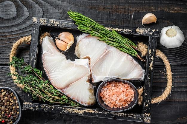 Haai rauwe vis steaks in een houten bakje met kruiden houten tafel. bovenaanzicht.