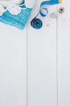 Haak en gebreide stof; meetlint; punaise; vingerhoed; draad en knop op houten tafel