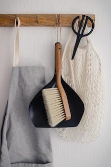 Haak hanger met zwarte schaar, grijze schort, eco tas, bezem en scoop opknoping op de muur in de keuken