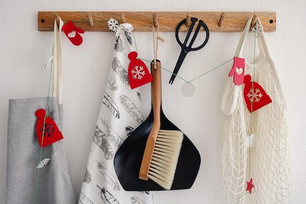 Haakhanger met met diverse huishoudelijke accessoires aan een witte muur in de moderne keuken