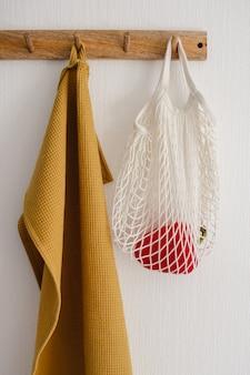 Haakhanger met witte eco tas met paprika en gele katoenen handdoek, hangend aan een witte muur in de moderne keuken