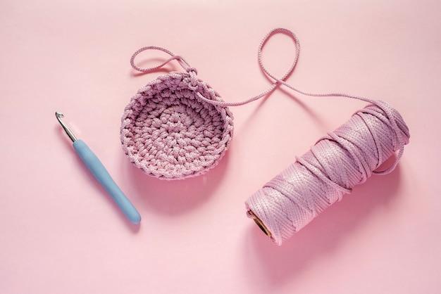 Haaknaald en roze kleurgaren op een roze achtergrond, brei- en haakbenodigdheden, hobby en handwerk