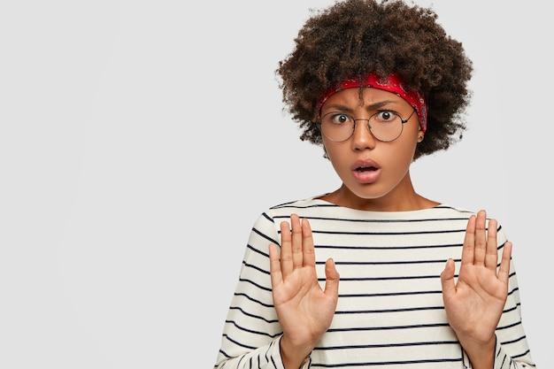 Haal het van me weg! ontevreden zwart meisje trekt handpalmen in stopgebaar, voelt zich ongelukkig