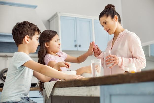 Haal het weg. vrij ellendig donkerharig meisje dat ontbijt met haar broer en weigert vitamines te slikken en haar moeder kijkt strikt