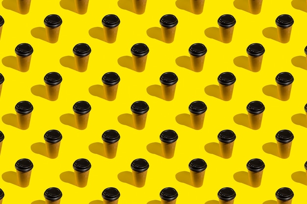 Haal koffie uit een bruine thermokop op een felgele achtergrond. koffiekopje op geel abstract patroon. Premium Foto