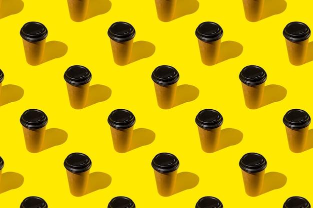 Haal koffie uit een bruine thermokop op een felgele achtergrond. koffiekopje op geel abstract patroon.