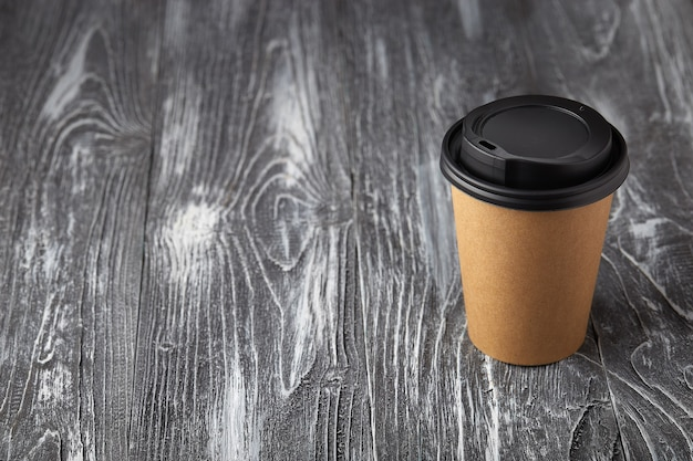 Haal papieren koffiekopje op grijze houten achtergrond in een hoek bekijken