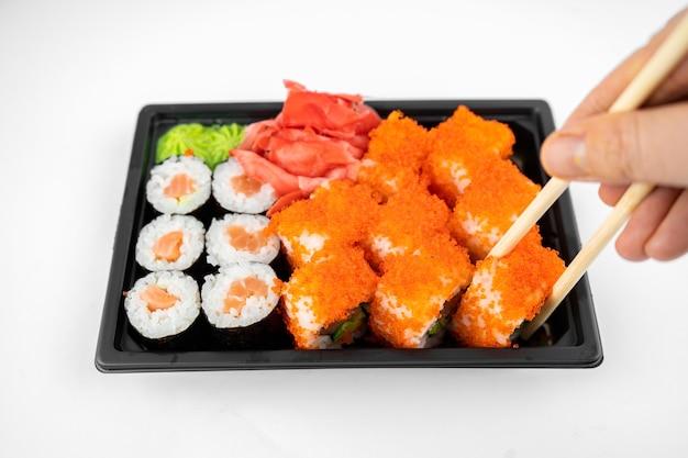 Haal sushirolletjes weg in een plastic bakje, california, zalm makirol, roze gember, wasabi. sushi levering concept