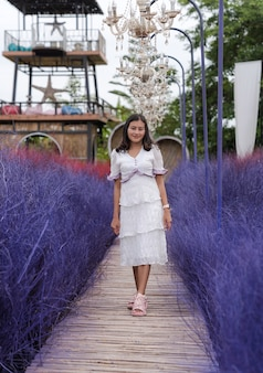 Haappy aziatische vrouw die op een houten brug loopt tussen de kleurrijke, paarse, droge grasherfsttuin