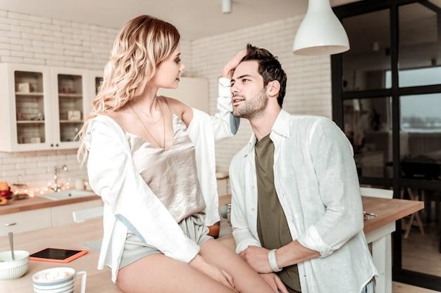 Haar aanraken. glimlachende jonge langharige mooie vrouw die een wit overhemd draagt dat het haar van haar echtgenoot aanraakt