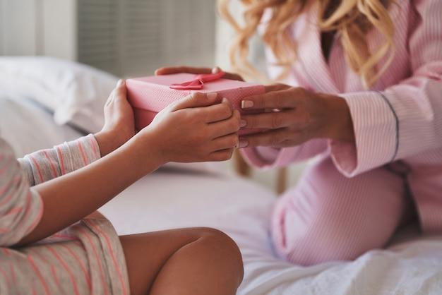 Haar dochter blij maken. close-up van een jonge moeder die een cadeautje geeft aan haar dochtertje terwijl ze thuis op bed zit