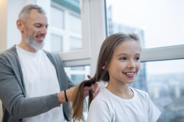 Haar doen. een grijsharige vader die haar haar doet bij zijn dochter