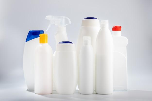 Haar- en lichaamsreinigers en badkamer- en glazenwassers. huishoudelijke chemicaliën op een witte muur.