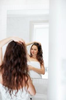 Haar- en lichaamsverzorging. mooie jonge vrouw haar natte haren met handen aan te raken en glimlachen terwijl staande voor de spiegel in de badkamer. meisje gebruikt bescherming vochtinbrengende crème.