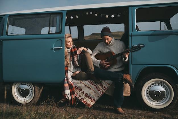 Haar favoriete liedje spelen. knappe jongeman gitaarspelen voor zijn mooie vriendin zittend in blauwe retro-stijl minibusje