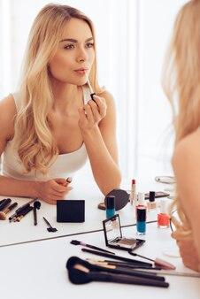 Haar favoriete lippenstift. mooie jonge vrouw die lippenstift aanbrengt en naar haar spiegelbeeld kijkt terwijl ze aan de kaptafel zit